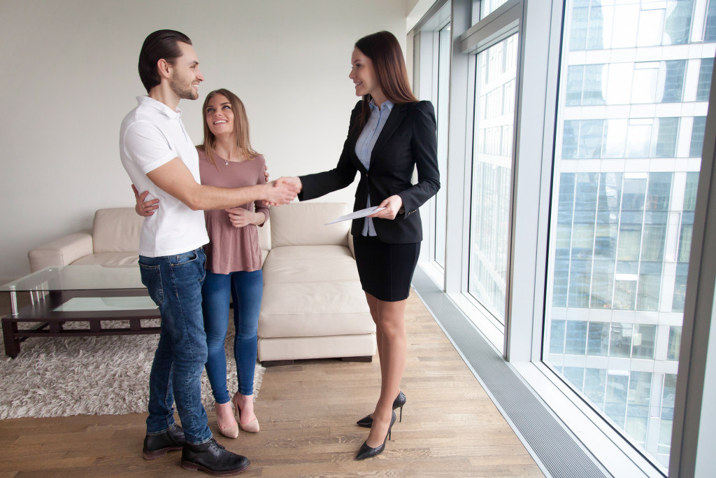 couple shaking hands with a realtor
